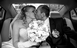 Portrait of bride and groom kissing at car Stock Photos