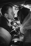 Portrait of bride and groom kissing in car Royalty Free Stock Image