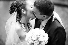 Portrait of bride and groom kissing outdoors Stock Photography