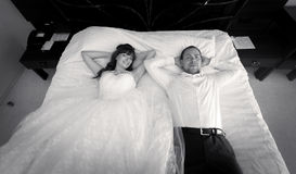 Portrait of bride and groom lying on big bed at hotel Royalty Free Stock Photo