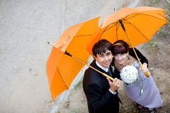 Portrait of bride and groom with orange umbrellas Stock Photo