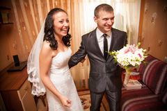 Portrait of bride and groom smiling in living room Royalty Free Stock Photo