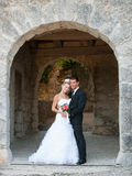 Portrait of bride and groom under stone arch Stock Photo