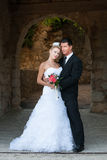 Portrait of bride and groom under stone arch stock photos