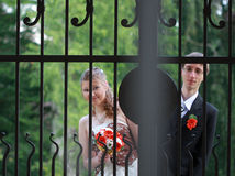 Portrait of bride and groom view through gate Royalty Free Stock Images