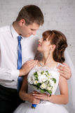 Portrait of the bride and groom on the white brick wall stock photos