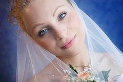 Portrait of the bride holding a bouquet. The bride holds a bouquet and pensively looks royalty free stock photo