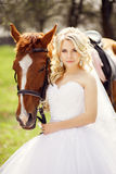 Portrait of a bride with a horse in a spring garden Stock Images