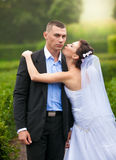 Portrait of bride kissing groom in cheek at park Stock Images