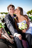 Portrait of bride kissing groom at coach Royalty Free Stock Images