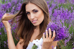 Portrait of  bride at purple lavender field. Closeup portrait of beautiful smiling girl at field of purple lavender flowers with flying hair Stock Photo