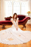 Portrait of bride sitting on floor by window Stock Photography