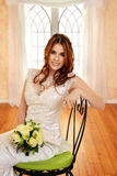 Portrait bride sitting on metal chair with green cushion Royalty Free Stock Photos