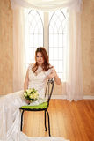 Portrait of bride sitting on metal chair by window Royalty Free Stock Photo