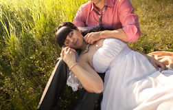 Portrait of bride sleeping on grooms knees at field Royalty Free Stock Photo