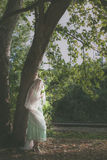 Portrait of bride with veil and bouquet of wild flowers outdoor. Shot stand by tree  summer day Stock Photography