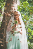 Portrait of bride with veil and bouquet of wild flowers outdoor. Shot stand by tree  summer day with leaves falling Royalty Free Stock Image