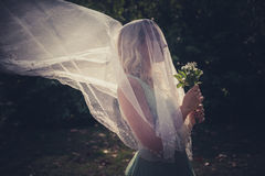 Portrait of bride with veil and bouquet of wild flowers outdoor. Shot  summer day outdoor Stock Photos