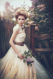 Portrait of a bride in a white dress with flowers in retro style. Beautiful bride in a white dress with flowers in retro style is on the nature of the summer Royalty Free Stock Images