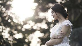 Portrait of a bride in a white wedding dress on a background of blurred green bushes and trees. Action. Sensual brown. Portrait of a bride in a white wedding stock video footage