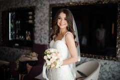 Portrait of bride in white wedding dress and bouquet with roses Stock Images