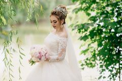 Portrait of a bride who walks in nature. The girl looks down and demonstrates her beautiful soft makeup and long stock image