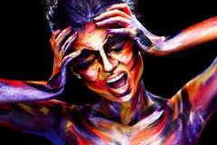 Portrait of the bright beautiful girl with art colorful make-up and bodyart. Portrait of the bright beautiful young woman with art make-up on dark background stock photo