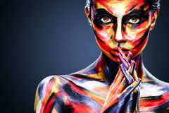 Portrait of the bright beautiful girl with art colorful make-up. Portrait of the bright beautiful young woman with art make-up on dark background stock images
