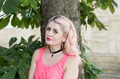 Portrait of a bright blonde to pink at the tree stock images