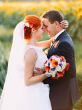 Portrait of bright happy redhair bride and handsome groom lovingly look at each other in the sunny sunflower field Stock Image
