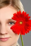 Portrait of a bright woman holding a red flower. Bright portrait of a young woman holding a red flower near the face Royalty Free Stock Photos