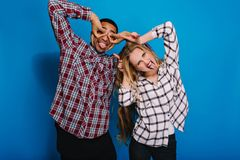 Portrait brightful positive emotions of funny excited couple fooling around on blue background. Having fun, free time. Showing tongue, caper, monkey, funny royalty free stock photo