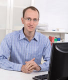 Portrait of broker with glasses in blue shirt at desk at office. Stock Photo
