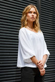 Portrait of brooding blonde girl in white blouse outdors. Portrait of brooding blonde girl in white blouse near gray wall outdors Royalty Free Stock Photography