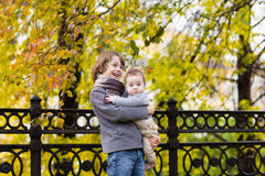 Portrait of brother and baby sister with a colorful yellow leaves Stock Photography