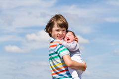 Portrait of a brother hugging his baby sister with cloudy sky Royalty Free Stock Photo