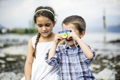 Portrait of a brother and sister children with toy camera. In summer outdoor royalty free stock photo