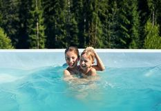 Portrait of brother and sister fooling around in outdoor pool Royalty Free Stock Photo