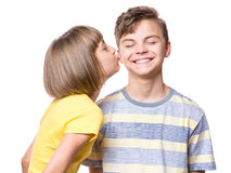 Portrait of brother and sister. Friendship - beautiful girl kissing teen boy. Portrait of happy brother and sister, isolated on white background. Funny couple Stock Photos