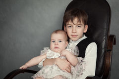 Portrait of brother and sister on gray background. Portrait of older brother and younger sister, family, photo studio on gray background, children sit in chair Royalty Free Stock Image