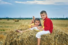 Portrait of brother and sister in the manger. Children on a walk in the countryside . Children`s outdoor recreation stock images