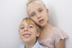 Portrait of brother and sister over gray background Stock Photos