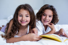 Portrait of brother and sister reading book together on bed Royalty Free Stock Photo