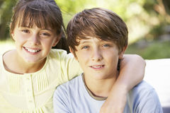 Portrait Of Brother And Sister Sitting In Garden Together Royalty Free Stock Images