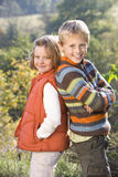 Portrait of brother and sister standing back to back Royalty Free Stock Photo