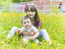 Portrait of brother and sister together sitting in dandelion field. Outdoor Stock Photo