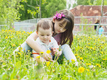 Portrait of brother and sister together sitting in dandelion field. Outdoor Royalty Free Stock Image