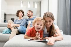 Family in Evening. Portrait of brother and sister using digital tablet and laughing while lying on sofa in living room with parents watching TV in background Royalty Free Stock Photos