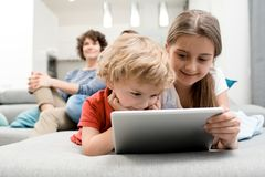 Little Children Using Tablet. Portrait of brother and sister using digital tablet lying on sofa in living room with parents watching TV in background Royalty Free Stock Photo