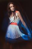 Portrait brouillé d'art de couleur d'une fille sur un fond foncé Façonnez la femme avec le beau maquillage et une robe légère d'é Photographie stock libre de droits